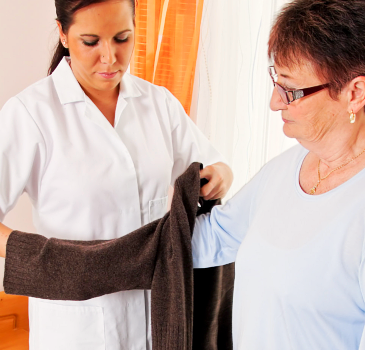 caregiver help in dressing the old woman