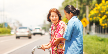 caregiver assisting the old woman to cross the street