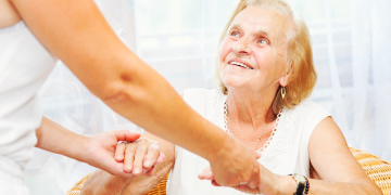 young woman hold the hands of the old woman