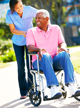 old man sitting on the wheelchair while the caregiver is giving him a tour