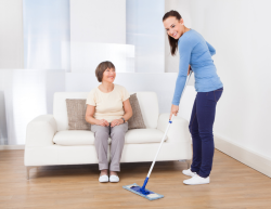 caregiver is sweeping in the floor while the old woman is sitting at the sofa