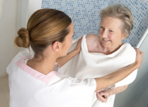caregiver is helping the old woman to take a bath